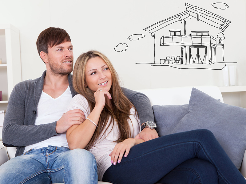 Cheerful young couple dreaming about the future sitting at couch